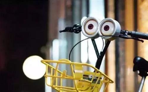 晚上骑行共享单车,遇对向灯光耀眼的汽车,正确做法是()
